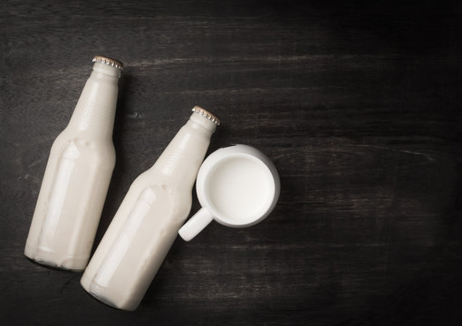 Milk cup and bottle milk on dark wooden table,Top view with copy space