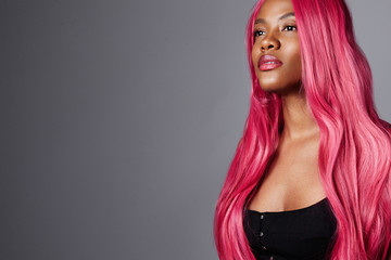 gorgeous black woman with braight pink hair. creative hair color concept