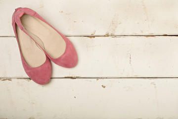 Pink women's shoes (ballerinas) on wooden background.