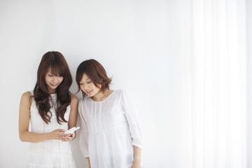 Two young women looking at mobile phone, copy space