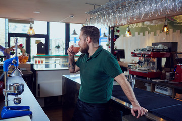 The bartender barista waiter with a glass of fresh juice is resting at workplace in  bar.