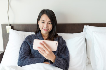 Woman watching movie on cellphone at bed