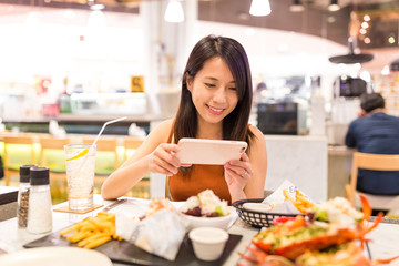 Woman taking photo on the dishes inside restaurant