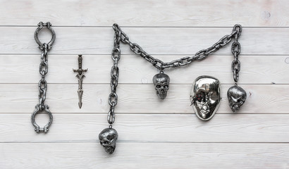 Chain with skulls, white wooden background, halloween.Shackles, daggers