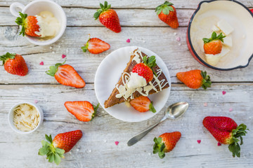 Brownie cake and fresh strawberries dipped in white chocolate.