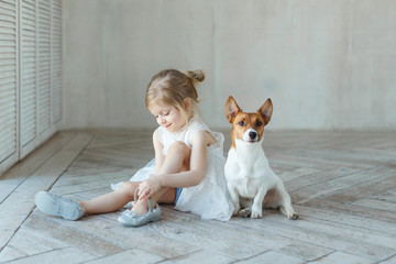 A girl sits on the floor in a room with a dog and brings the pointes