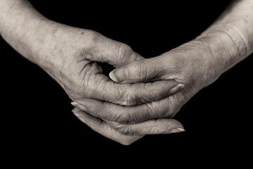 Close up of a pensioner's hands clasped. Monochrome.