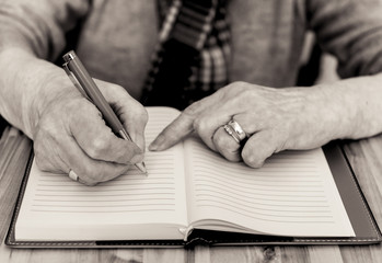 Elderly woman's hands writing in notebook. Black and white.
