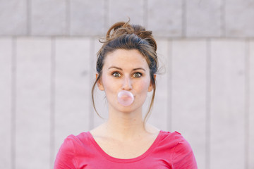 portrait of a funny young woman blowing pink gum