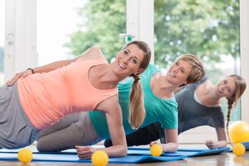 Frauen nach der Geburt machen Übungen für den Beckenboden im Rückbildungskurs