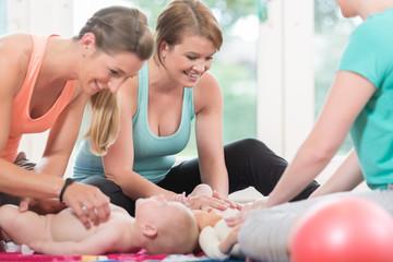 Junge Frauen nach der Geburt üben Baby wickeln im Mutter-Kind Kurs