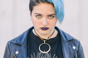 close up of a teen punk woman with a nose piercing, dyed blue hair and dark lips