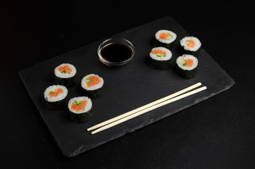 Sushi of norimaki with trout and cucumber on slate plate