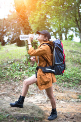 Hiker woman resting drinking water, select focus..