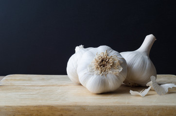 Garlic Bulbs Grouped on Chopping Board with Black Background