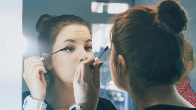 Woman applying black mascara on eyelashes with makeup brush. Young beautiful lady applying mascara makeup on eyes