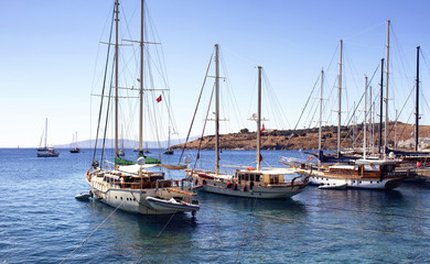 Luxury yachts (sailing boats) parked on turquoise water in front of Bodrum castle. The image shows Aegean and Mediterranean culture of coastal lifestyle.