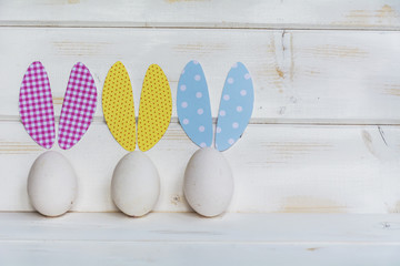 easter card with white  eggs with bunny ears on a white wooden background