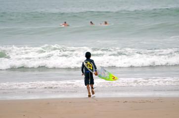 Little boy runs surfing in the ocean