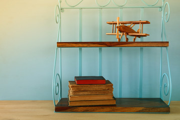 Vintage shelf with old wooden plane toy and books