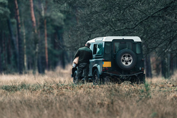 Ranger with jeep in field near forest. National Park Hoge Veluwe.