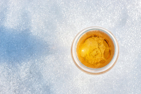 Glass of beer in the snow.