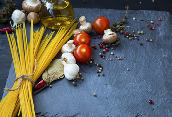 Raw spaghetti with sauce ingredients, garlic, spices,tomatoes, olive oil