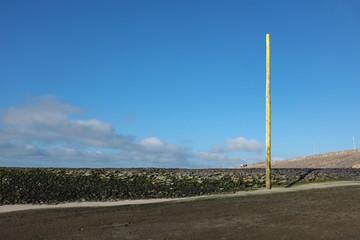 Poteau planté au bord de la plage.
