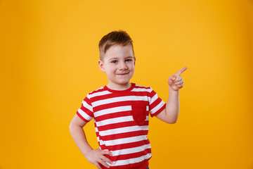 Smiling happy boy pointing finger up at copyspace Wall mural