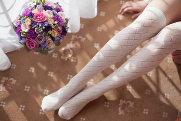Wedding bouquet and legs of the bride in white stockings