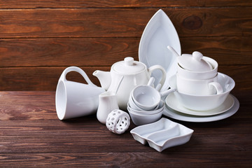 Set of new white dishes with teapot, tea cups, and plates on wooden table