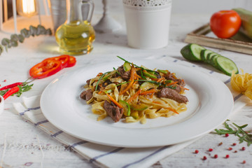 Pasta with olive meat greens on a white plate