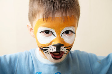 Children face painting. Roaring boy painted as tiger or ferocious lion by make up artist. Preparing for theatrical performance. Boy actor playing role. Tiger mask face