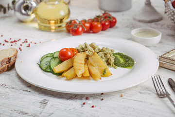 Chicken and potatoes with pickled cucumbers, greens
