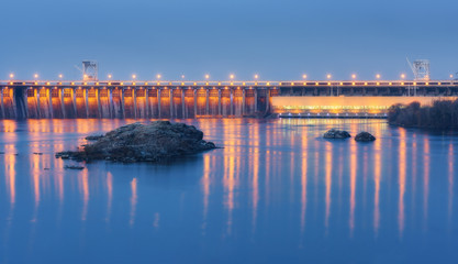Photo sur Plexiglas Barrage Dam at night. Beautiful industrial landscape with dam hydroelectric power station, bridge, river, city illumination reflected in water, rocks and sky. Dniper River, Zaporizhia, Ukraine.
