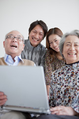 Senior Couple and Adult Daughter and Son Using Laptop