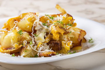 Fries with smashed eggs and parmesan with herbs