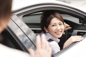 Senior woman talking to her daughter in car, smiling