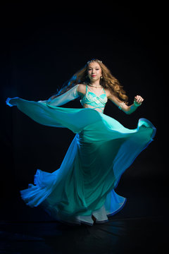 Portrait of a young girl with long hair in a turquoise costume oriental dancer dancing on a black background in the scenic blue light