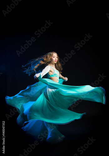 5762432993d Portrait of a young girl with long hair in a turquoise costume oriental  dancer dancing on a black background in the scenic blue light