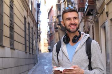 Handsome man joyfully exploring a city