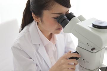 Young Female Scientist Using Microscope in Laboratory