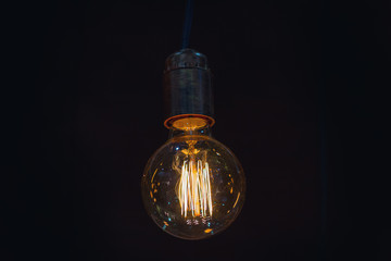 Vintage incandescent lamp hanging on a dark background