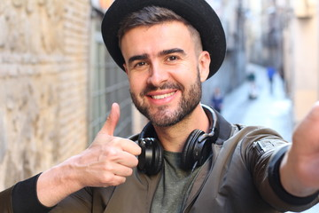Trendy handsome man taking a selfie and giving a thumbs up outdoors