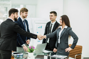 handshake of business partners after signing the contract in the