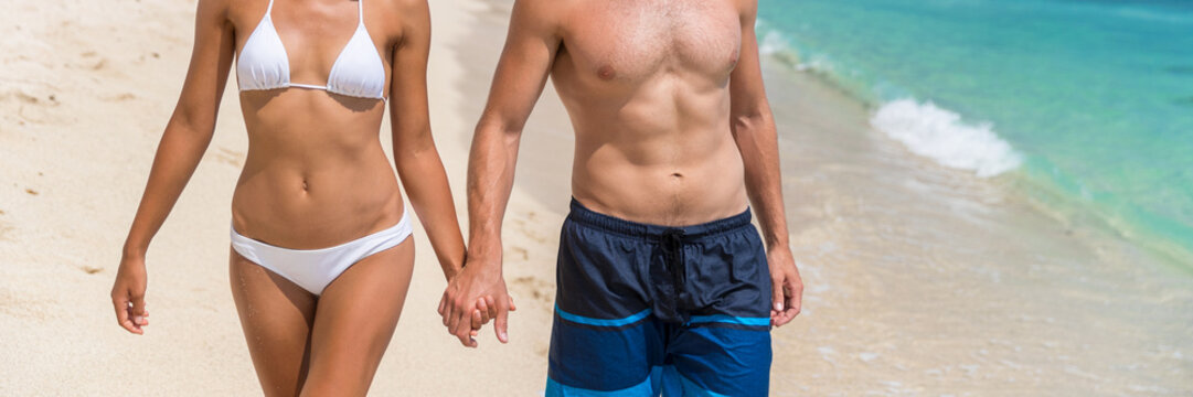 Body care sexy people in swimwear on beach banner background. Couple holding hands, woman in bikini, man in swim trunks showing toned abs stomach for healthy fitness concept.