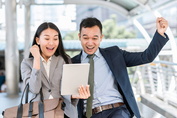 Young happy Asian businessman and woman celebrated success while looking in tablet outdoor.
