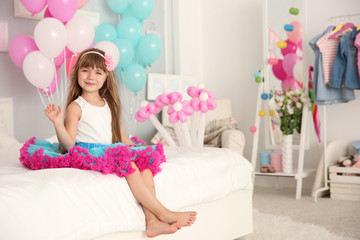 Cute girl sitting on bed in room decorated for birthday celebration