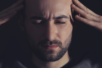 Handsome man suffering from headache on dark background, closeup