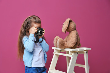 Little girl with vintage camera taking photo of toy on color background